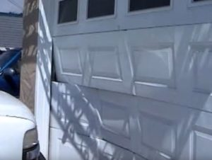 garage door that has been hit by a car